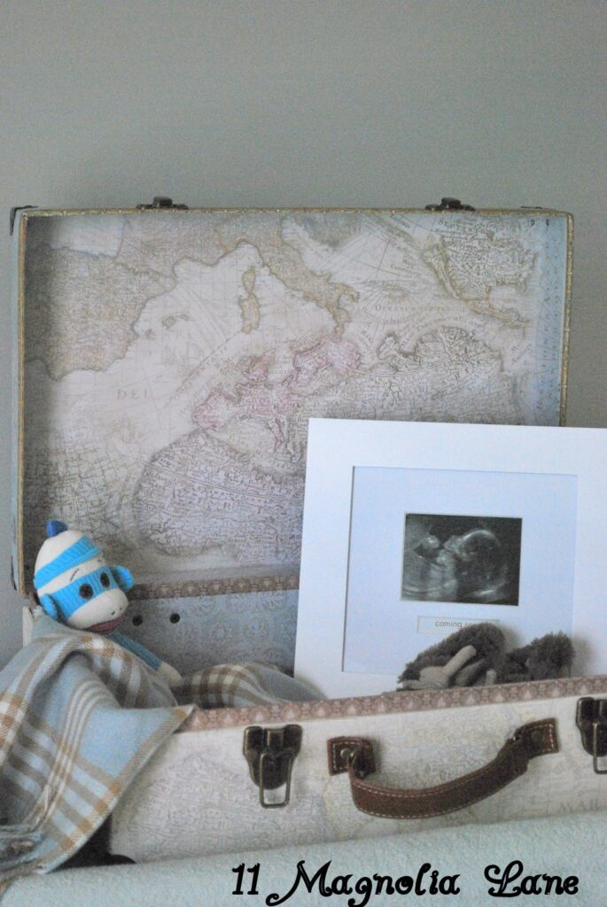Vintage Map Suitcase filled with a beautiful plaid blanket (thank you Amy) , toy money (Thank You Grammy) and his sonogram photo.