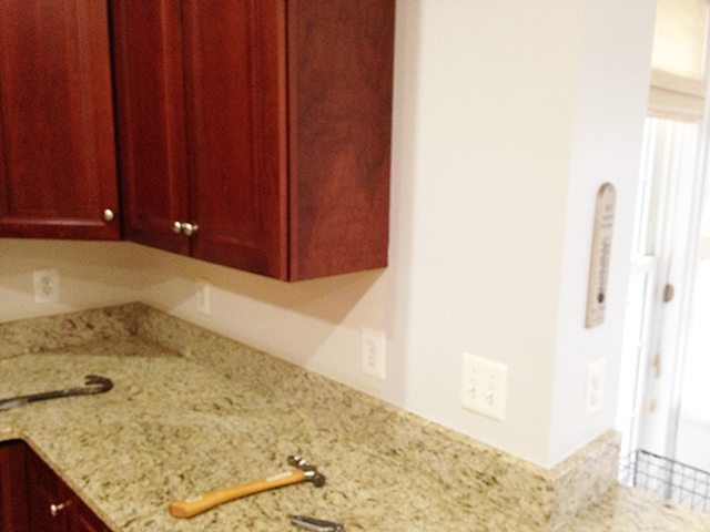 installing a new cararra marble tile backsplash in the